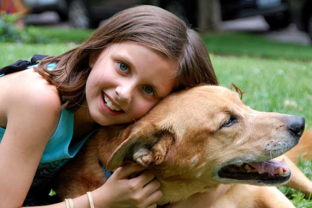 A girl hugging her dog outdoors