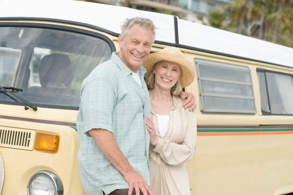 Man and woman posing with their campervan
